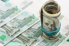Amerikanische Dollar auf einem Hintergrund des russischen Geldes Lizenzfreie Stockbilder