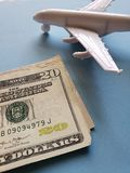 amerikanische Dollar Banknoten, weißes Plastikflugzeug und blauer Hintergrund lizenzfreies stockbild