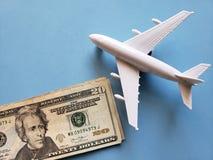amerikanische Dollar Banknoten, weißes Plastikflugzeug und blauer Hintergrund stockbild