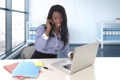 Amerikanische Ethniefrau des Schwarzafrikaners, die am Computerlaptop am Schreibtischlächeln glücklich arbeitet stockbilder