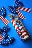 Amerikanische Feiertagsflaggenbögen und -Kracher stockbild