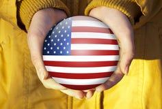 Amerikanische Flagge in den Händen Stockbild