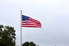 Amerikanische Flagge, die auf Pfosten wellenartig bewegt stockfotos