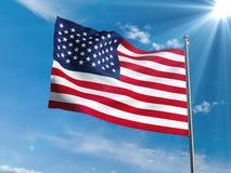 Amerikanische Flagge, die in blauen Himmel mit Sonne wellenartig bewegt Stockfotos