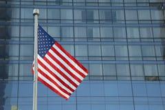 Amerikanische Flagge, die in das Stadtzentrum einer bedeutenden Stadt wellenartig bewegt stockfotos
