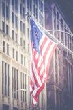Amerikanische Flagge, die in die Brise in der im Stadtzentrum gelegenen Schleife Chicagos wellenartig bewegt Stockfotografie
