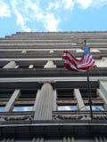 Amerikanische Flagge, die an einem windigen Tag, Ansicht gerade schaut oben von direkt unten, vor historischer Bürogebäudefassade stockfotografie