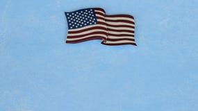 Amerikanische Flagge, die flach auf einen blauen Hintergrund legt stockfotos
