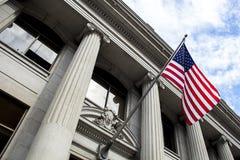 Amerikanische Flagge, die im Wind vor Steinsäulegebäude mit blauem Himmel und Wolken durchbrennt stockfotos
