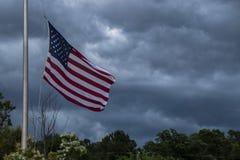 Amerikanische Flagge, die mit Sturm-Wolken wellenartig bewegt Lizenzfreie Stockbilder