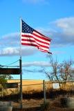 Amerikanische Flagge gegen das goldene Feld und den glänzenden Himmel Stockfotografie