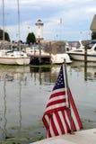 Amerikanische Flagge im Hafen mit Booten und Leuchtturm Lizenzfreies Stockbild