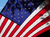 Amerikanische Flagge mit der Sonne, die durch scheint Stockfotos