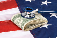 Amerikanische Flagge mit Stapel des Bargeldes und des Stethoskops Stockfotos