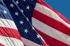 Amerikanische Flagge schmückte mit Sternenbanner Wellen im Wind gegen einen blauen Himmel Lizenzfreie Stockbilder