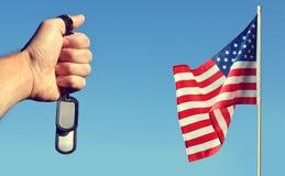 Amerikanische Flagge und Hand mit Soldaten etikettiert auf blauem Himmel Lizenzfreie Stockfotografie