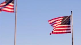 Amerikanische Flaggen beim Flaggenpfostenwellenartig bewegen