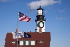 Amerikanische Flaggen, die vor Leuchtturm wellenartig bewegen Stockbild