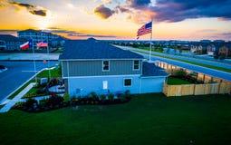 Amerikanische Flaggen mit Neuentwicklungs-Vorort und Texas Flag bei Sonnenuntergang stockfotos