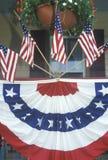 Amerikanische Flaggen und mit dem Kopfe stoßendes Hung auf Portal des Hauses Lizenzfreie Stockfotografie