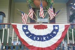Amerikanische Flaggen und mit dem Kopfe stoßendes Hung auf Portal des Hauses Stockfotografie