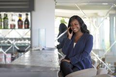 Amerikanische Frau des attraktiven und glücklichen Schwarzafrikaners, die von der Restaurantbar spricht am Handy arbeitet stockfoto