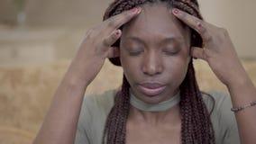 Amerikanische Frau des nervösen Afroamerikaners mit Dreadlocks ihren Kopf mit den Fingern massierend Dame hat starke Kopfschmerze stock video
