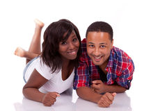 Amerikanische Paare des glücklichen jungen Schwarzafrikaners, die sich auf dem floo hinlegen Lizenzfreies Stockbild