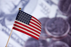 Amerikanische Spielzeugmarkierungsfahne über Dollarbanknoten. Stockfotos