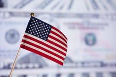 Amerikanische Spielzeugmarkierungsfahne über Dollarbanknoten. Lizenzfreies Stockfoto