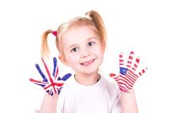 Amerikanische und englische Flaggen auf den Händen des Kindes. lizenzfreies stockfoto