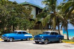 Amerikanischer blauer Chevrolet- und Buick-acht Oldtimer mit weißem Dach parkte auf dem Strand unter Palmen in Varadero Kuba - Se Stockbilder