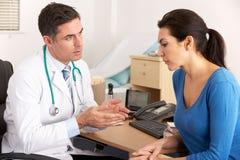Amerikanischer Doktor, der mit Frau in der Chirurgie spricht Lizenzfreie Stockfotos