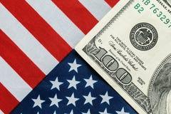 Amerikanischer Dollar auf der amerikanischen Flagge Stockfotografie