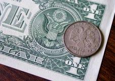 Amerikanischer Dollar und russische Münze Stockbilder