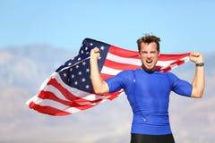 Amerikanischer Erfolgsmannathlet, der mit USA-Flagge gewinnt Stockfoto