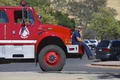 Amerikanischer Feuerwehrmann, der auf dem Stoßdämpfer eines Löschfahrzeugs sitzt Stockbilder
