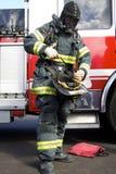 Amerikanischer Feuerwehrmann, der geht, einen Sturzhelm zu tragen Stockfoto