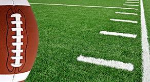 Amerikanischer Fußball auf Arena nahe der Yard-Line 50 lizenzfreie stockfotos