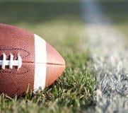 Amerikanischer Fußball auf dem Feld mit grünem Gras Stockfotografie