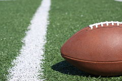 Amerikanischer Fußball auf künstlichem Grasfeld Stockbilder
