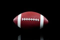 Amerikanischer Fußball auf Schwarzem lizenzfreie stockfotos