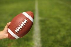Amerikanischer Fußball in der Hand Lizenzfreie Stockbilder