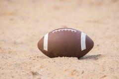 Amerikanischer Fußball im Sand auf dem Strand stockfotos