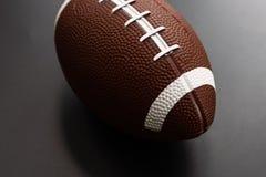 Amerikanischer Fußball lokalisiert auf schwarzem Hintergrund Sportgegenstandkonzept stockbild