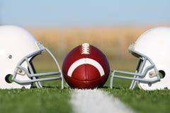 Amerikanischer Fußball mit Sturzhelmen auf dem Feld Lizenzfreies Stockbild