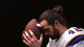 Amerikanischer Fußball-Spieler der, leicht seinen Ball zu halten und zu küssen und liest geistlich ein Gebet vor dem Match stock video footage