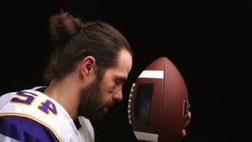 Amerikanischer Fußball-Spieler der, leicht seinen Ball zu halten und zu küssen und liest geistlich ein Gebet vor dem Match stock video