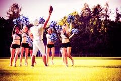Amerikanischer Fußball-Spieler mit Cheerleadern Stockbild