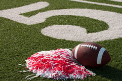 Amerikanischer Fußball und Pom Poms auf Feld Stockbild